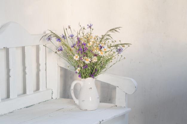 Fleurs sauvages en pot sur banc en bois blanc