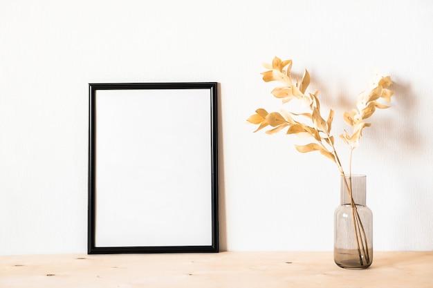 Fleurs séchées et un cadre photo contre un mur lumineux