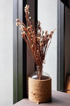 Fleurs séchées de couleur marron dans des bouteilles transparentes enveloppées avec des cordes.
