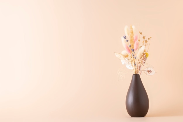 Fleurs séchées dans un vase sur fond beige ou crème avec espace de copie.