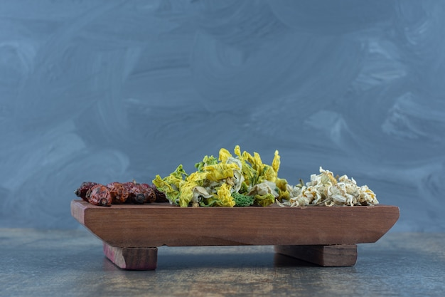 Fleurs séchées et églantier sur planche de bois.