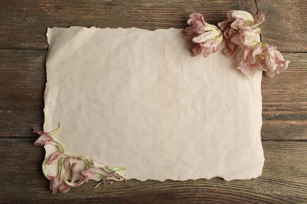 Fleurs séchées sur feuille de papier sur table en bois, vue du dessus