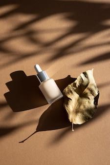 Fleurs séchées et fond de teint avec des ombres naturelles sur fond pastel nature morte cosmétique pour...