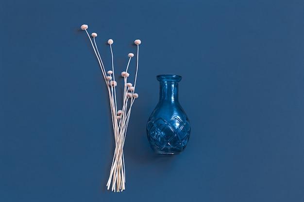 Fleurs séchées et un vase sur bleu.