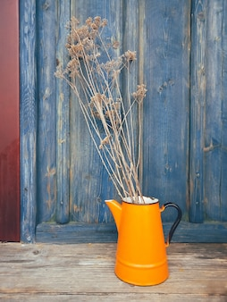 Fleurs sèches dans une cruche en métal orange
