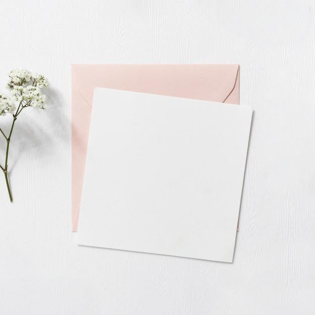Fleurs de souffle de bébé et enveloppe rose et blanche sur fond blanc