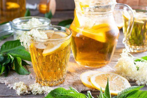 Fleurs de sureau et boisson au citron. jus d'été sain et rafraîchissant. verre de limonade aux fleurs de sureau sur planche rustique en bois. médecine alternative et thérapie.