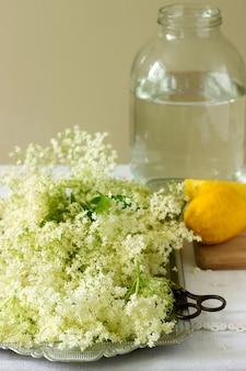 Fleurs de sureau, eau, citron et sucre, ingrédients pour faire du sirop de sureau. style rustique.
