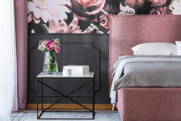 Fleurs sur table noire à côté d'un lit rose et gris à l'intérieur de la chambre avec papier peint. vrai photo
