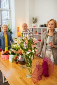 Fleurs tendres. mise au point sélective de fleurs debout dans le vase avec des gens qui les regardent