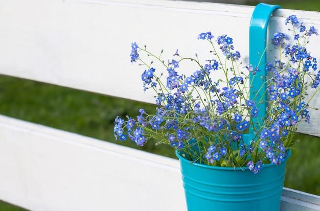 Fleurs tendres partiellement floues sur une surface en bois rustique. un bouquet de myosotis sur les vieilles planches. espace de copie.