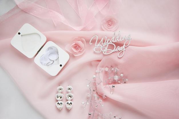 Fleurs en tissu décoratif, bijoux de mariée sur mousseline rose sur fond de papier blanc