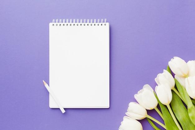 Fleurs de tulipes blanches et bloc-notes vide