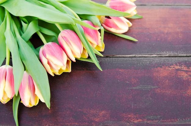Fleurs de tulipes jaunes roses sur planche de bois