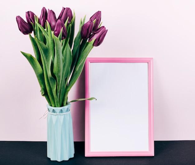 Fleurs de tulipes pourpres fraîches dans un vase avec cadre photo bordure rose