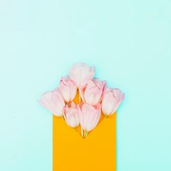 Fleurs de tulipes roses dans l'enveloppe sur la table