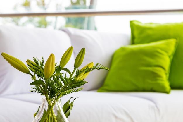 Des fleurs vertes comme décoration intérieure et un canapé blanc avec des coussins verts