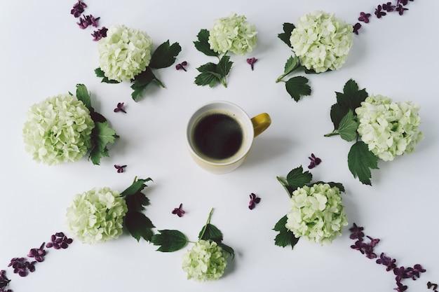 Fleurs vertes et pétales de lilas sous la forme d'un cercle se trouvant autour de la tasse jaune avec du café sur fond blanc