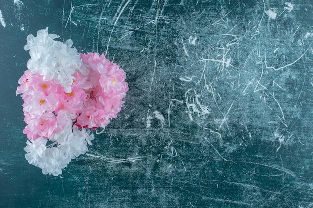 Fleurs violettes et blanches dans un seau rose, sur fond blanc.