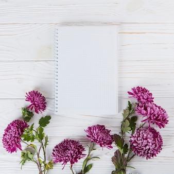 Fleurs violettes avec cahier vierge sur une table en bois