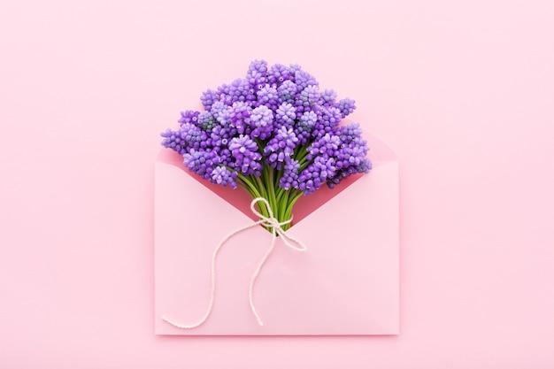 Fleurs violettes de printemps dans une enveloppe rose