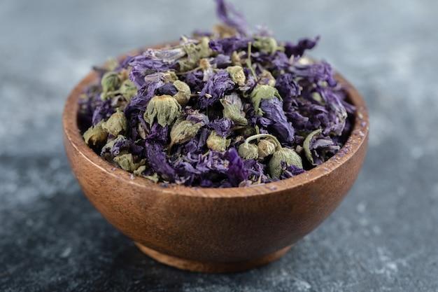 Fleurs violettes séchées dans un bol en bois.
