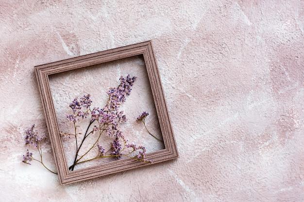 Fleurs violettes sèches dans un cadre en bois sur un fond texturé. carte vintage de voeux romantique. vue de dessus. espace de copie