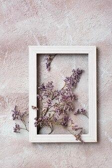 Fleurs violettes sèches dans un cadre en bois sur un fond texturé. carte vintage de voeux romantique. vue de dessus et verticale