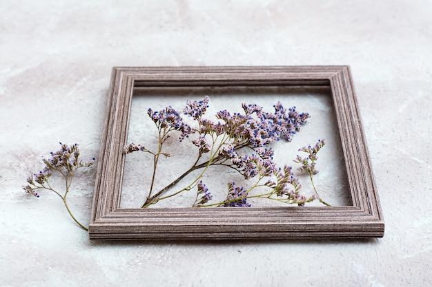 Fleurs violettes sèches dans un cadre en bois sur un fond texturé. carte vintage de voeux romantique