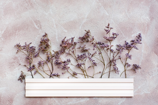 Fleurs violettes sèches derrière une bordure en bois blanche sur un fond texturé. carte vintage de voeux romantique. vue de dessus