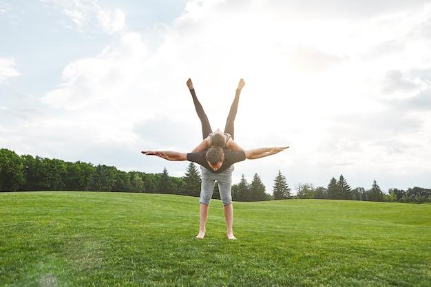 Flexibilité du yoga jeune couple en bonne santé faisant du yoga acro sur une herbe en bonne santé le matin ensoleillé