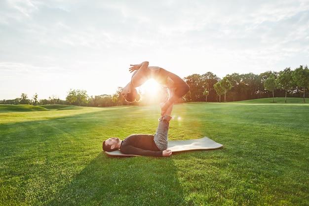 Flexibilité parfaite beau couple pratiquant le yoga acro ensemble à l'extérieur sur un homme du matin ensoleillé