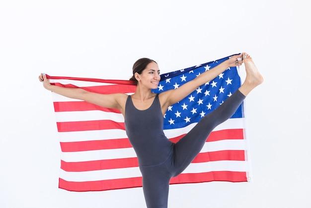 Flexible femme heureuse athlète drapeau américain usa independence day 4 juillet