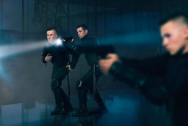 Flics avec des fusils habillés en uniforme et gilet pare-balles