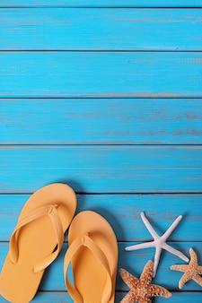 Flip flops étoiles poisson été bord de mer bleu fond bois vertical