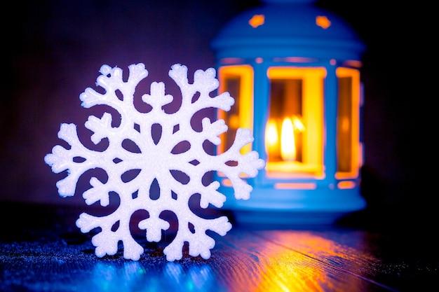 Flocon de neige blanc décoratif près de lanterne avec bougie