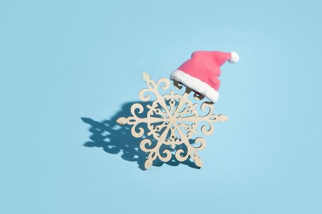 Flocon de neige en bois en bonnet de noel sur fond bleu