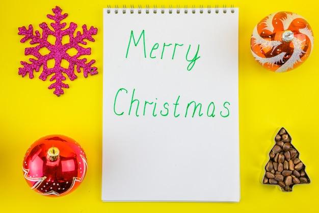 Flocon de neige, boules de noël, un arbre de noël fait de noix d'épinette et un cahier avec l'inscription de joyeux noël.