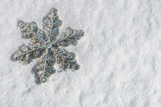 Flocon de neige décoratif sur la neige pour les vacances de noël