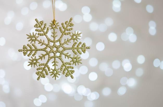 Flocon de neige doré est suspendu à une branche d'arbre de noël