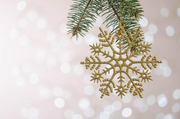 Un flocon de neige jouet doré est suspendu à une branche d'arbre de noël. bokeh. décoration de noël