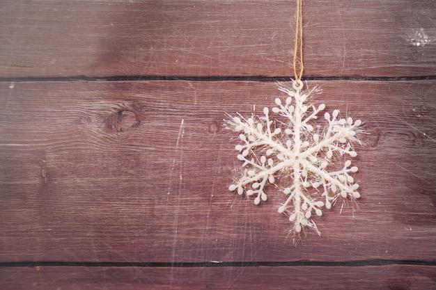 Flocon de neige de noël blanc argenté sur fond en bois vintage. image tonique