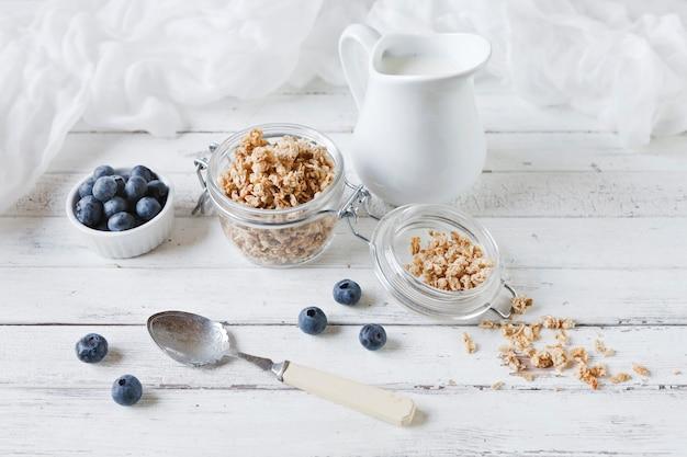 Flocons d'avoine et bleuets frais au lait. petit déjeuner délicieux, sain et utile sur fond de table en bois blanc. vue de dessus, gros plan.