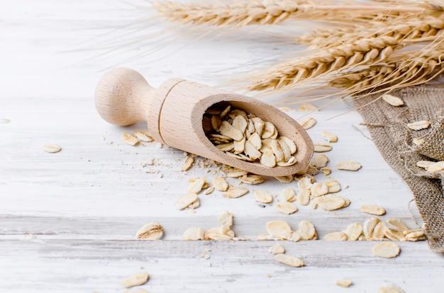 Flocons d'avoine à la cuillère en bois sur fond sombre
