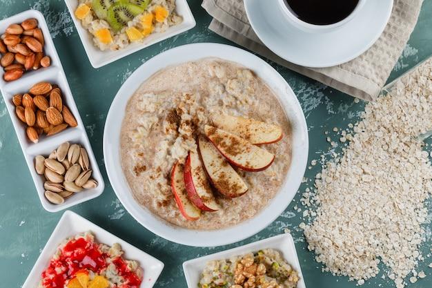 Flocons d'avoine dans des assiettes avec fruits, confiture, noix, cannelle, café, flocons d'avoine