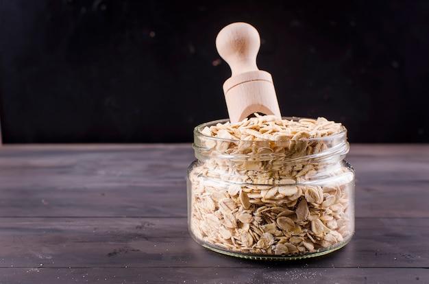 Flocons d'avoine dans un bocal en verre et une cuillère en bois