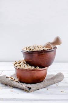 Flocons d'avoine dans un bol en céramique et une cuillère en bois