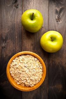 Flocons d'avoine dans un bol et deux pommes