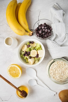 Flocons d'avoine dans un bol et fruits. lait et miel. fond de ciment. vue de dessus. composition à plat