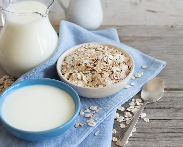 Flocons d'avoine dans un bol et lait sur une table en bois se bouchent